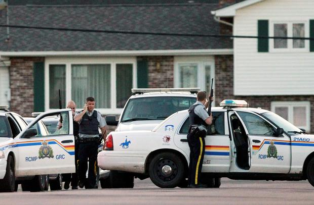 Codiac RCMP officers take cover behind their vehicle in Moncton, New Brunswick June 4, 2014. Three police officers were shot dead and two more were wounded, police said as they conducted a manhunt for a man carrying a rifle and wearing camouflage clothes. Police said they were searching for Justin Bourque, 24, of Moncton. REUTERS/Viktor Pivarov/Moncton Times & Transcript