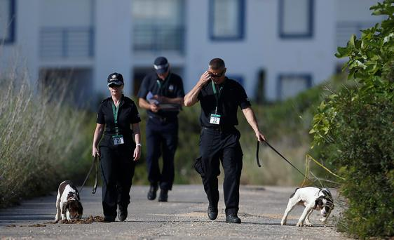 Scotland Yard detectives work with sniffer dogs on an area during the search for missing British girl Madeleine McCann