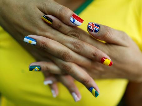 A woman shows her nails after being painted with the flags of countries that will participate in the 2014 World Cup in Brazil. Photo: REUTERS/Pilar Olivares