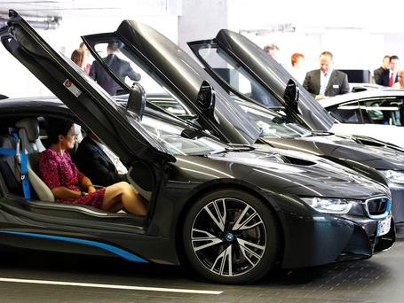 The world's first eight costumers of the new BMW i8 plug-in hybrid sports car receive instructions during the official delivery in Munich, Germany. Photo: REUTERS/Michaela Rehle