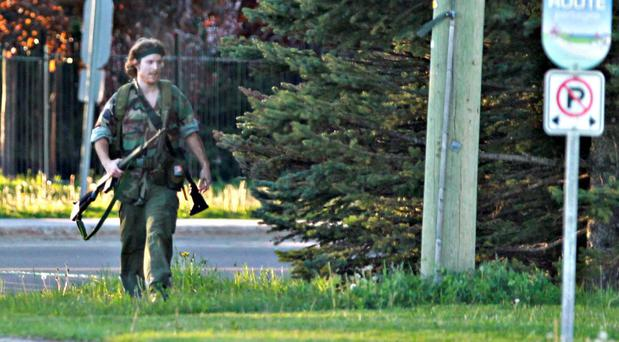 The heavily armed man that police have identified as Justin Bourque walks on Hildegard Drive in Moncton, New Brunswick, on Wednesday
