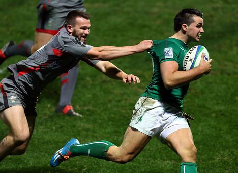 Cian Kelleher of Ireland beats the tackle of Afon Bagshaw of Wales during the 2014 Junior World Championship match between Wales and Ireland