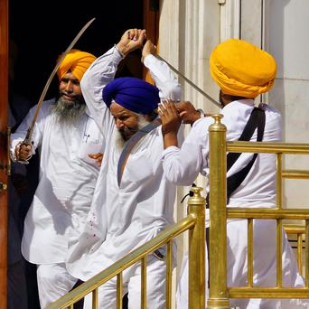 Sikhs wield swords during their clash inside the complex of the holy Sikh shrine, the Golden Temple, in the northern Indian city of Amritsar
