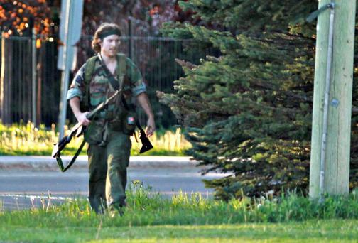 A heavily armed Justin Bourque walks on Hildegard Drive in Moncton, Canada