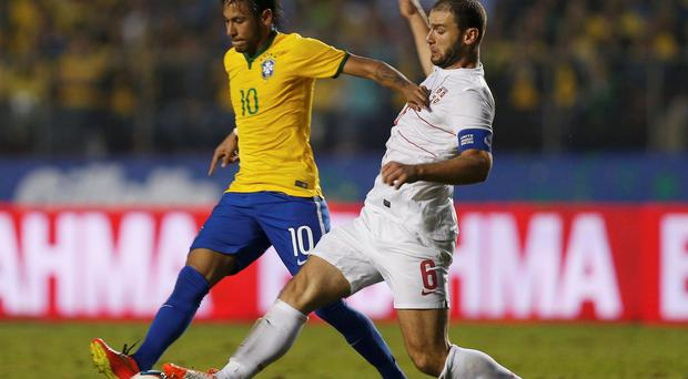 Brazil's Neymar (L) battles Serbia's Branislav Ivanovic during their international friendly soccer match ahead of the 2014 World Cup in Morumbi stadium in Sao Paulo