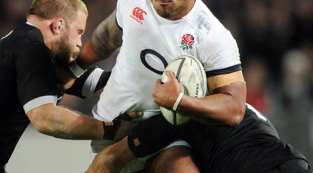 Englands Manu Tuilagi, center, attempts to bust the tackle of New Zealands Owen Franks, left, and Richie McCaw