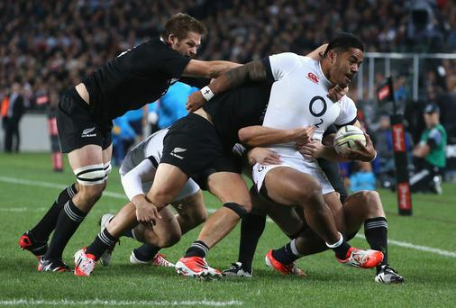 Manu Tuilagi of England is hauled down by the All Black defence.