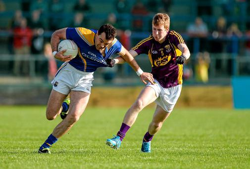 Wexford's Michael Furlong gets to grips with Longford's Paul Barden during last night's Leinster SFC clash. Photo: Oliver McVeigh / SPORTSFILE