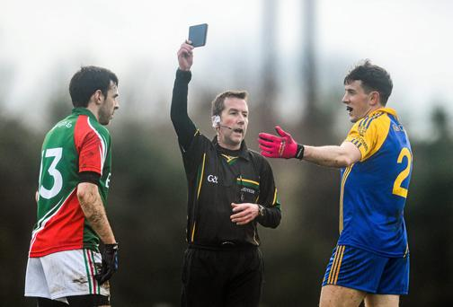 Referee Eamonn O'Grady shows the black card to Neill Collins