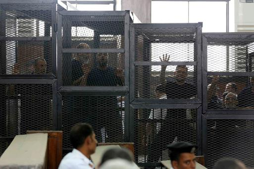 Muslim Brotherhood's General Guide Mohamed Badie (R) is pictured in a defendant's cage with other defendants in a courtroom in Cairo June 7, 2014. An Egyptian court sentenced 10 supporters of the outlawed Muslim Brotherhood to death in absentia on Saturday but postponed sentencing of its leader and other senior members tried in the case, judicial sources said. Judge Hassan Fareed said the verdict for the rest of the defendants, including Badie, would be announced at a hearing on July 5. REUTERS/Mohamed Abd El Ghany (EGYPT - Tags: CRIME LAW POLITICS)