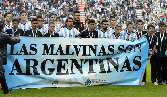 "Argentina's footballers pose for photographers holding a banner reading ""The Malvinas are Argentinian"" before a friendly against Slovenia at La Plata stadium in Buenos Aires"