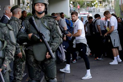 England captain Steven Gerrard, center, and goalkeeper Joe Hart, right, pass members of the Brazilian army standing on guard as the players got off the team coach upon their arrival at the squad's hotel for the 2014 World Cup in Rio do Janeiro. AP