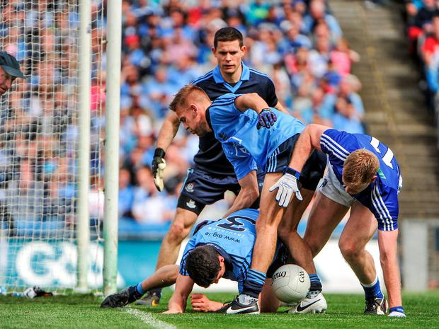 Rory O'Carroll and Jonny Cooper, Dublin, vie for possession with Donal Kingston, Laois