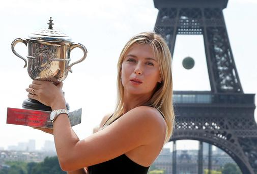 Russia's Maria Sharapova poses with the trophy in front of the Eiffel Tower, one day after defeating Romania's Simona Halep in the women's final of the French Open tennis tournament in Paris