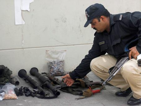 A policeman arranges weapons seized after an attack on Jinnah International Airport in Karachi. Reuters