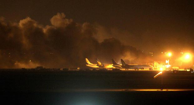 Fire illuminates the sky above the Jinnah International Airport in Karachi where security forces fought with Taliban militants on Sunday night in Pakistan. AP