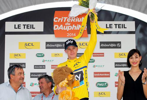 Christopher Froome of Great Britain and Team Sky, wearing the yellow leaders jersey, celebrates on the podium after the third stage of the Criterium du Dauphine between Ambert and Le Teil, France
