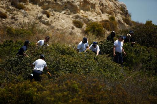 Members of Scotland Yard work at an area during the search for missing British girl Madeleine McCann
