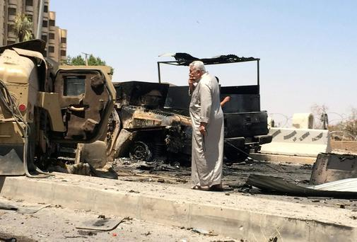 A man looks at burnt vehicles belonging to Iraqi security forces one day after radical Sunni Muslim insurgents seized control of city of Mosul