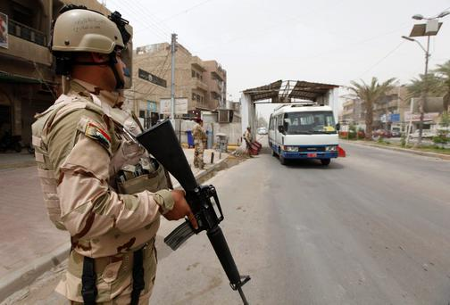 An armed member of the Iraqi security forces stands at a checkpoint, as security increases in Baghdad