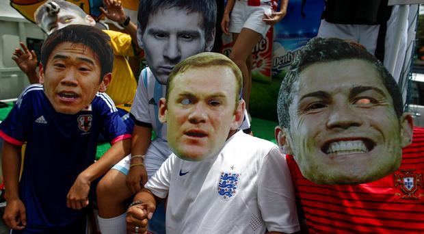 Fans wearing masks of famous soccer players pose for a photo as they celebrate ahead of the 2014 World Cup, at a shopping district in Bangkok June 12, 2014. REUTERS/Athit Perawongmetha