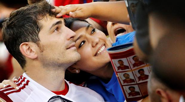 A supporter reaches out to touch the hair of Spain's national soccer team goalkeeper Iker Casillas