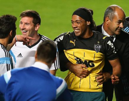 A fan bearing the resemblance of Ronaldinho is escorted off the field while talking to Lionel Messi