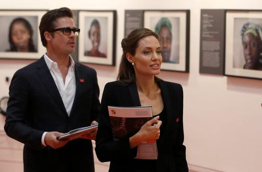 Angelina Jolie and her partner, actor Brad Pitt peruse photographs. Photo: Reuters/Luke MacGregor