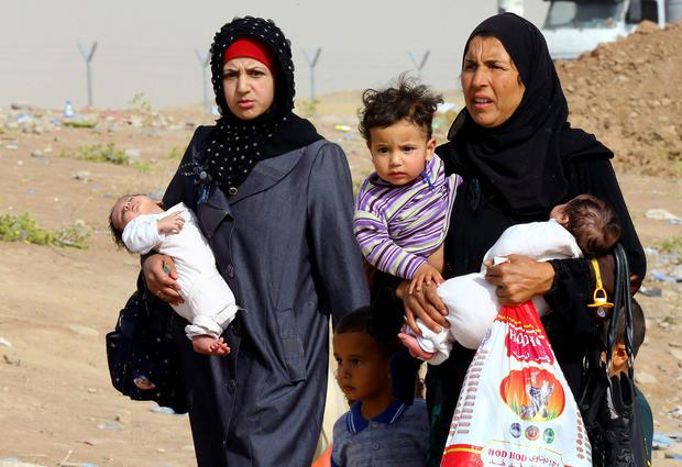 Iraq refugees fleeing from Mosul head to the self-ruled northern Kurdish region, as they walk past an area in Irbil, Iraq, 350 kilometers (217 miles) north of Baghdad. AP