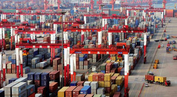 Trucks drive past piles of shipping containers at Qingdao port in Qingdao, Shandong province
