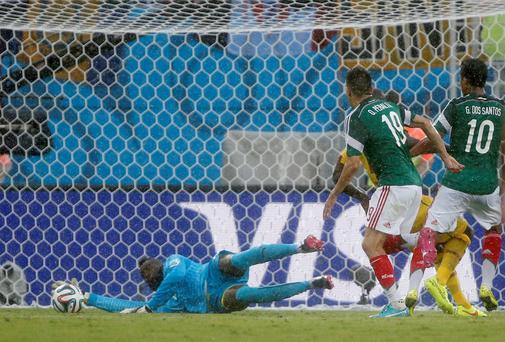 Mexico's Oribe Peralta follows up to score the opening goal during the group A World Cup soccer match between Mexico and Cameroon in the Arena das Dunas in Natal