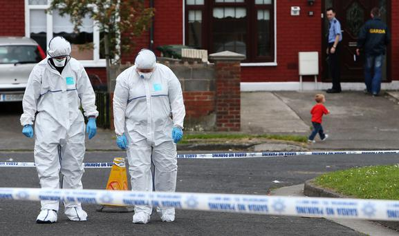 Members of the Garda forensic team at the crime scene in Croftwood Gardens, Dublin, where a six-year-old boy was shot last night. Photo: Brian Lawless/PA Wire