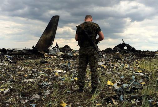 A pro-Russian fighter guards the site of remnants of a downed Ukrainian army aircraft Il-76 at the airport near Luhansk, Ukraine. Pro-Russian separatists shot down the military transport plane Saturday in the countrys restive east, killing all 49 service personnel on board, Ukrainian officials said.