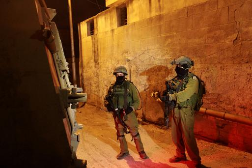 Israeli soldiers stand guard during a military operation to search for three missing teenagers near the West Bank city of Hebron
