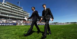 Aidan O'Brien and his son Donncha O'Brien walk the course at Epsom racecourse in Epsom, England.