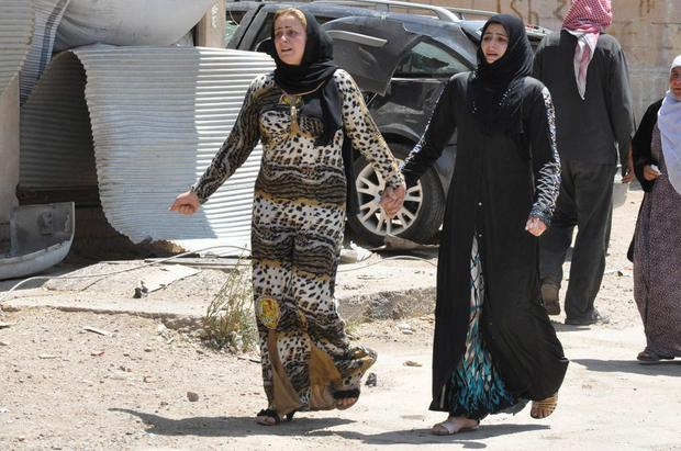 Women react at a damaged site in what activists said was caused by a suicide bomber in the middle of a market last night in Tirbespiye village, east Qamishli, June 15, 2014. Activists claim that 14 people died due to the explosion, seven of them are Arab and the other seven are Kurds, while 25 were injured. REUTERS/Massoud Mohammed