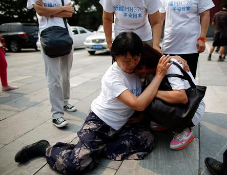 A family member of a passenger aboard the missing Malaysia Airlines flight MH370 comforts another relative as they gather to pray at Yonghegong Lama Temple in Beijing. Sunday marks the 100th day that the flight from Kuala Lumpur to Beijing disappeared with 239 passengers and crew on board.