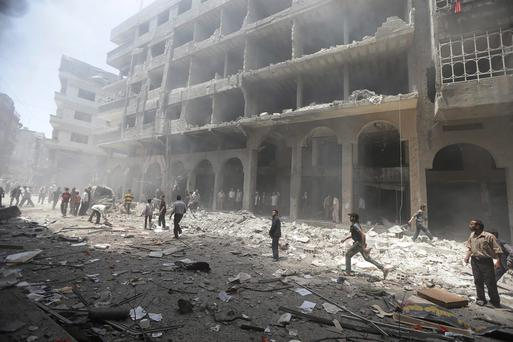 Residents run in a damaged site due to what activists claim was from shelling by forces loyal to Syrian President Bashar al-Assad at a market in central Duma in the eastern al-Ghouta, near Damascus