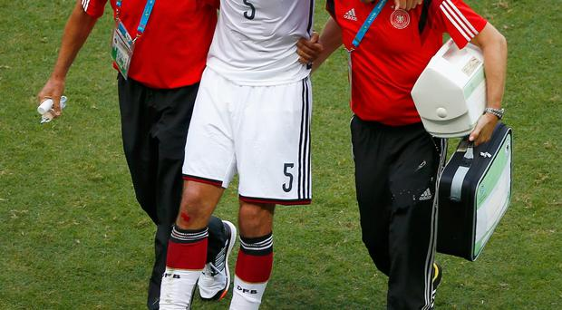 An injured Mats Hummels of Germany is helped off the field during the 2014 FIFA World Cup Brazil Group G match between Germany and Portugal