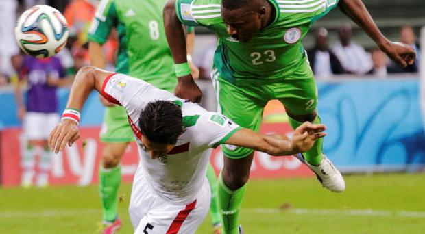 Nigeria's Shola Ameobi (R) fights for the ball with Iran's Amir-Hossein Sadeghi