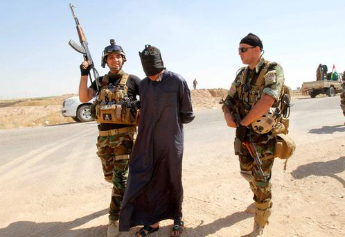 Personnel from the Kurdish security forces detain a man suspected of being a militant belonging to the al Qaeda-linked Islamic State in Iraq and the Levant (ISIL) in the outskirts of Kirkuk. Reuters