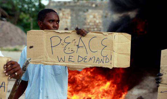 A resident holds a placard as he participates in a protest against the recent attack by unidentified gunmen in the coastal Kenyan town of Mpeketoni. Reuters