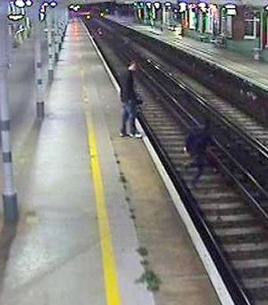 CCTV still of one of three men walking on railway tracks just inches from a live rail and minutes before a train arrived at Worthing railway station, West Sussex