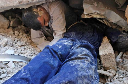 A man tries to pull an injured person trapped under the rubble of collapsed buildings at a site hit by what activists said was a barrel bomb dropped by forces loyal to Syria's President Bashar al-Assad in Aleppo's al-Ansari neighbourhood. Reuters/Hosam Katan