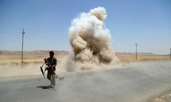 A member of the Kurdish security forces walks away from a controlled explosion in the town of Tuz Khurmato, north of the capital Baghdad, June 17, 2014. Picture taken 17, 2014. REUTERS/Yahya Ahmad (IRAQ - Tags - Tags: CIVIL UNREST POLITICS MILITARY)