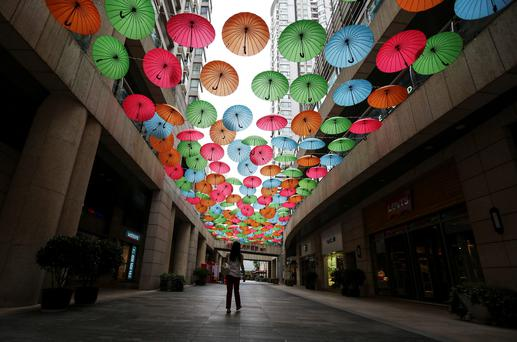A woman walks under a decoration made of coloured umbrellas at a shopping centre in downtown Kunming, Yunnan province