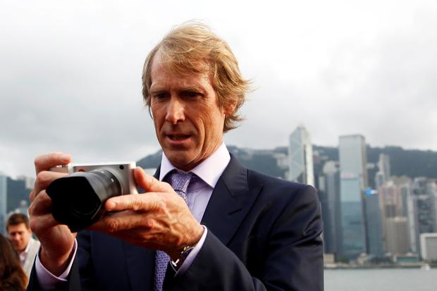 U.S. director Michael Bay takes pictures with his camera on the red carpet as he arrives for the world premiere of the film