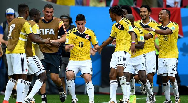 Colombia's James Rodriguez celebrates by dancing with teammates after scoring his team's first goal against the Ivory Coast