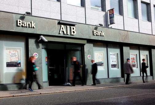 Pedestrians pass a branch of the Allied Irish Bank (AIB) in Dublin, Ireland