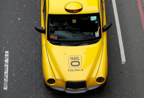A taxi displays an advertisement for electronic hailing application Hailo as it travels along Lower Thames Street during the morning rush hour in London, U.K